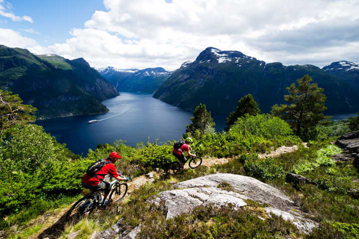 Tobias Liljeroth and Janne Tjärnström rides on the old Post route between Bergen and Trondheim, right above the Geiranger fjord near Hellesylt, Norway. The famous cruise ship Hurtigrutten is seen down in the fjord. Photographed in July